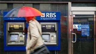Someone walking past a RBS cash machine