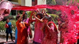 A bucket of red coloured water is thrown over a group of people