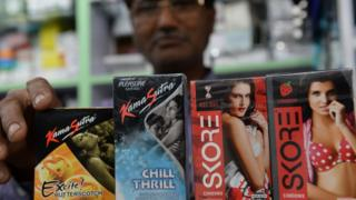 An Indian shopkeeper arranges condom packets at a chemist shop in New Delhi on April 27, 2016.