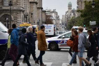Passerby walk as police vehicle drive toward Paris after a fatal knife attacks.
