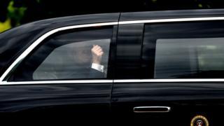 """特朗普总统随后前往克拉伦斯宫喝下午茶,他从他的""""野兽""""豪华轿车中举手示意。"""