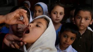 A Pakistani health worker gives a polio vaccine to a student at a school in Peshawar, Pakistan, Monday, April 18, 2016.