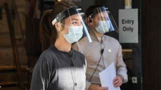 Shop workings wearing protective face visors in Sydney