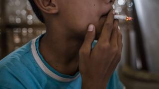 Teenager smokes at a kiosk on March 6, 2017 in Yogyakarta, Indonesia