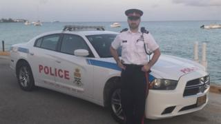 Matthew Thomas by a Cayman Island police car