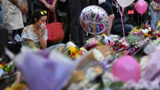 A woman weeps as she sits alongside a carpet of flowers and messages at St Ann's Square in Manchester following the terror attack on Manchester Arena