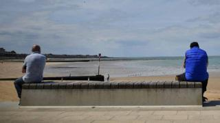 People social distance as the look towards Margate Sands beach in Margate south east England, on May 16, 2020