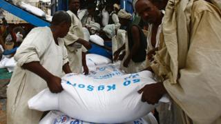Sudanese workers offload US aid destined for South Sudan from the World Food Programme (WFP)