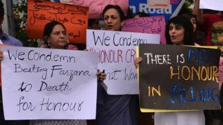 Pakistani human rights activists hold placards as they chant slogans during a protest in Islamabad on May 29, 2014 a