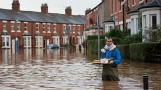 A man in a flooded street in Carlisle