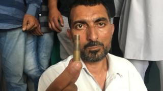 Abdul Rehman Mir holding a bullet case