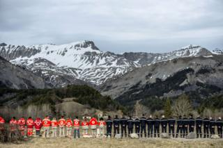 French rescue workers gather in front of a memorial for the victims of the Germanwings air crash in Le Vernet, south-eastern France, on March 28, 2015