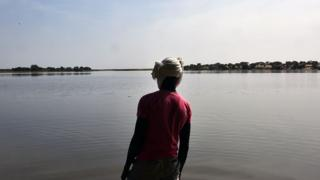 A survivor of a Boko Haram attack in Chad looking out over Lake Chad - archive