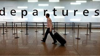 Man walking through departure lounge at airport