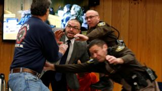 Court security staff try to shield Larry Nassar after the father of two of his victims lunged at him