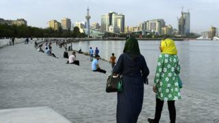 Two women in headscarves take a walk along Baku's seafront