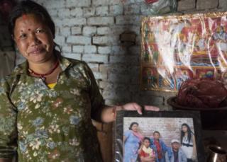 Chandra Kala Magar holds up a family photograph