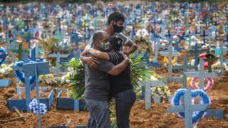 Relatives of a deceased person wearing protective masks mourn during a mass burial of coronavirus in Manaus