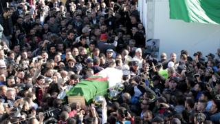 The coffin of Hocine Ait Ahmed, the Algerian leader of the Front of Socialist Forces party (FFS), is carried to be buried after prayers by his relatives and people in his hometown