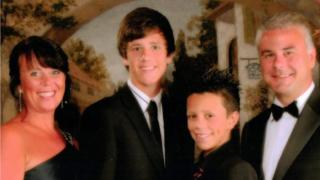 Four people in a photo from left to right. They are looking formally dressed. On the left is June, Jack Thomnas is on the second left and is wearing a suit and black tie, his younger brother Owain stands next to him - who is also smartly dressed and has spikey hair. On the right is the two boy's dad Grant. All are smiling in the photo and they appear to be standing in front of a painting depicting a European country village.