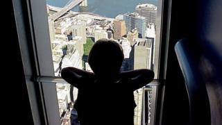 Criança olha cidade da janela de um apartamento