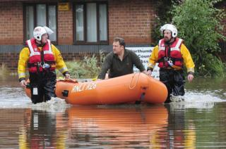 A resident is taken to safety aboard a dinghy