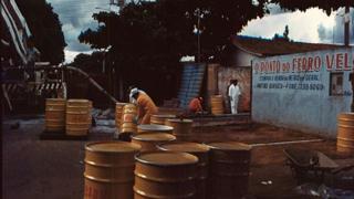 Imagem mostra toneis posicionados em frente a ferro-velho contaminado em acidente radiotivo em 1987, no Brasil, e homens trabalhando no processo de descontaminação no local