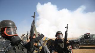 Иракские военные в защитных масках возле горящего химического завода