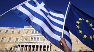 A Greek and EU flag are waved in Athens