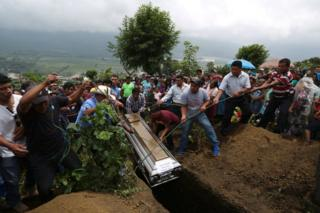 A coffin is lowered into the ground with ropes