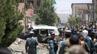 In this Friday, Aug. 7, 2015, photo, Afghan security personal inspect at the site of a suicide car bomber has targeted a NATO convoy in Kabul, Afghanistan.