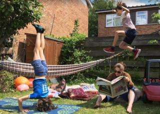 Woman reads paper in garden as two children play around her