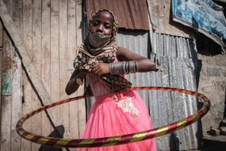 A girl in a pink dress smiles as she plays with a shiny hula hoop.