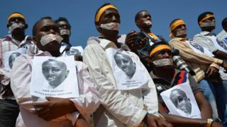 Somali journalists take part in a protest condemning their colleague's long term in jail, with their hands handcuffed and mouths covered with tape