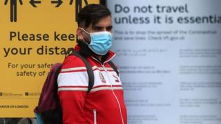 Man standing in a London bus stop wearing a face mask