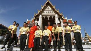 Members of Wild Boar youth soccer team and their coach-turned-Buddhist monk Ekapol Chantawong (back, C) visit Wat Phra Kaew or Temple of the Emerald Buddha within the Grand Palace complex in Bangkok, Thailand,