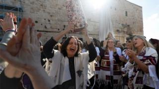 "A member of the liberal Jewish religious movement ""Women of the Wall"" dances with a Torah scroll at the egalitarian prayer section on the southern side of Judaism's holiest prayer site of the Western Wall in the Old City of Jerusalem on 8 March 2019"