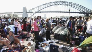 A crowd of people camp in front of the Sydney Harbour Bridge on New Year's Eve