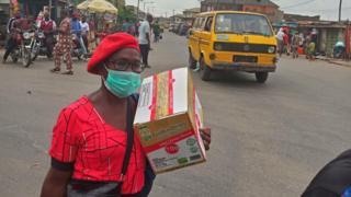 Woman wear mask carry carton for Lagos, Nigeria