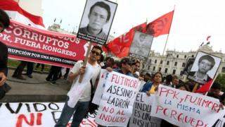 People holding banners and pictures of victims of the guerrilla conflict in the 1990s protest at Mr Fujimori's pardon (25/12/2017)