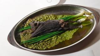 Un murciélago servido en una fuente sobre vegetales