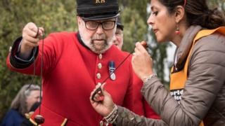A Chelsea Pensioner wearing his uniform competes with a woman wearing a puffer jacket.