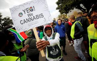 A demonstrator holds a placard during a march calling for the legalisation of cannabis, known locally as dagga, in Cape Town, South Africa