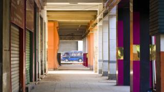 حافلة صغيرة في نهاية شارع تحفه أعمدة ملونة
