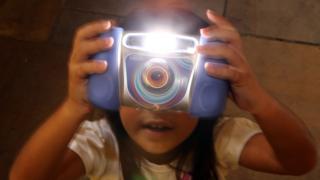 child holding vtech camera