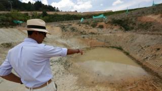 Hombre con sombrero señala un lugar donde se realizó una excavación.