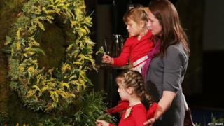 A mother and her two children pin flowers to a wreath in memory of MH17 victims, Canberra, 17 July 2015