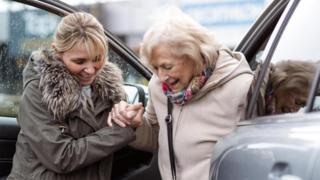 شابة تحاول مساعدة سيدة مسنة