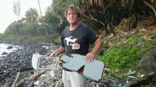 An undated handout photograph made available on 10 June 2016 by Blaine Alain Gibson showing Blaine Gibson holding new pieces of debris possibly belonging to the missing Malaysian Airlines plane MH370