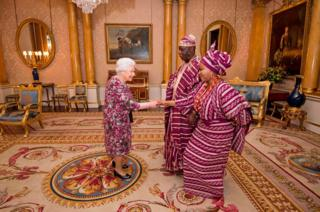 Britain's Queen Elizabeth II greets Nigerian High Commissioner George Adesola Oguntade and his wife Mrs Oguntade